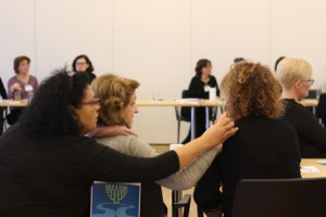 A guide-interpreter doing haptic sign for a deafblind woman during another guide-interpreter is interpreting her